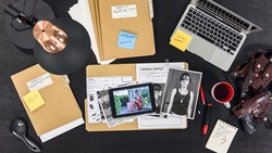 The detective works with criminal files and documents. View from above