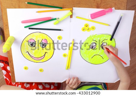 the development of emotional intelligence. child psychology. the girl and the boy draw happy and sad emoticons