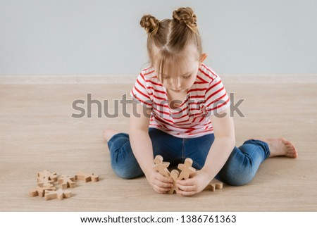 The development of soft skills in the child. Girl playing with wooden figures. #1386761363