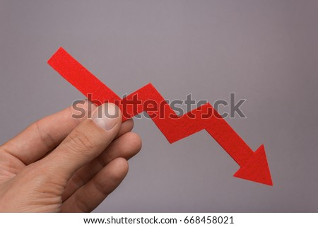 The diagram chart falls down in the hand. Success is in your hands. A paint arrow down in the person's hand against a gray background. Reduced price #668458021