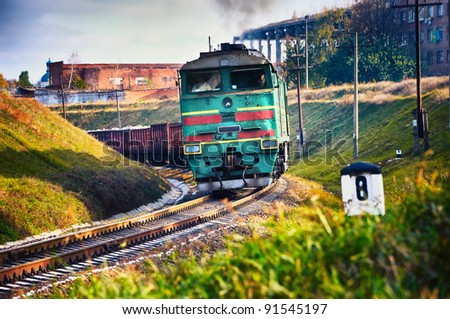 The diesel train with wagon goes on a curve. Cargo transportation in tanks by rail