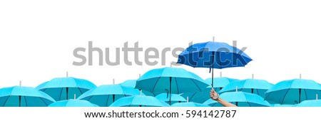 The difference to step up to leadership in business.blue umbrella among sky umbrellas. hand of man holding a blue umbrella over many umbrellas in raining. side view. #594142787