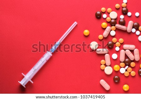 The different pills and syringe on red background.