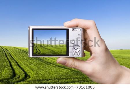 The digital camera in a hand. Landscape