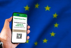 The digital green pass of the european union with the QR code on the screen of a mobile held by a hand with a blurred EU flag in the background. Immunity from Covid