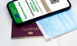 The digital green pass of the european union with the QR code on the screen of a mobile phone over a surgical mask and a passport. Immunity from Covid-19. Travel without restrictions.