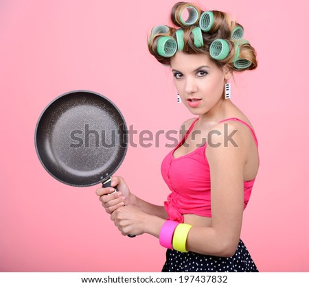 The dinner is almost ready. Sexy young housewife holding an empty pan - stock photo