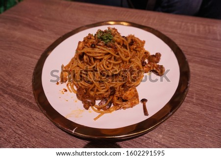 The dinner table have a plate of spaghetti.