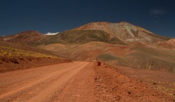 The dirt road high in the Andes mountains. Traveling along the route across the arid desert and mountain range. The sand and death valley under a deep blue sky in La Rioja, Argentina.