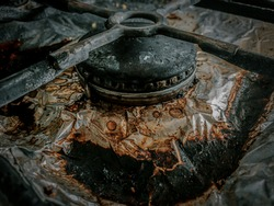 The Dirty and Grimy and Rusted Top of Gas Cooker Hob with Bits of Foil Underneath the Metal