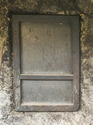 The dirty window of an old abandoned peasant house. Clay peasant house