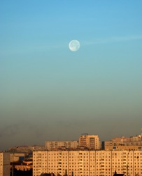 The disk of the moon over the city, early in the morning at dawn. Snapshot with natural light.