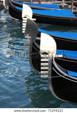 The distinctive prows of Venetian gondolas jostle side by side at the quay near San Marco's in the heart of Venice.
