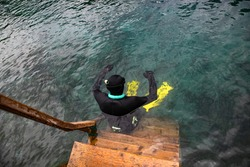 the diver is preparing to dive. Diving on a Blue lake with emerald water. Scuba diving training on the blue lake in Kazan