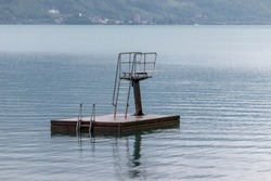 The diving board in the Walenstadt side of the Walensee is seen with Mols in the background on a rainy, quiet day in Switzerland.