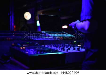 The DJ opens music at night to entertain people in the club. #1448020409