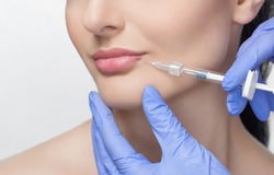 The doctor cosmetologist makes Lip augmentation procedure of a beautiful woman in a beauty salon.Cosmetology skin care.