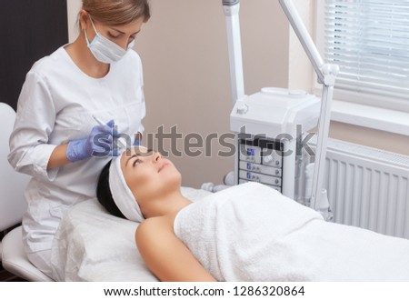 The doctor-cosmetologist makes the procedure treatment of Couperose of the facial skin of a beautiful, young woman in a beauty salon.Cosmetology and professional skin care. #1286320864