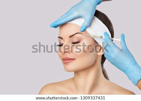 The doctor cosmetologist makes the Rejuvenating facial injections procedure for tightening and smoothing wrinkles on the face skin of a beautiful, young woman in a beauty salon.Cosmetology skin care. #1309337431