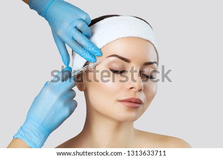 The doctor cosmetologist makes the Rejuvenating facial injections procedure for tightening and smoothing wrinkles on the face skin of a beautiful, young woman in a beauty salon.Cosmetology skin care. #1313633711