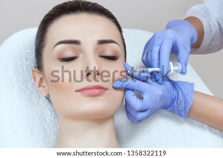 The doctor cosmetologist makes the Rejuvenating facial injections procedure for tightening and smoothing wrinkles on the face skin of a beautiful, young woman in a beauty salon.Cosmetology skin care. #1358322119