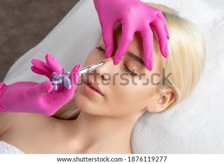 The doctor does injections to correct the hump on the nose with the beauty of the blonde. The beautician doees injections against wrinkles on the face. Women's cosmetology in a beauty salon. Photo stock ©