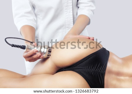 The doctor does the Rf lifting procedure on the legs, buttocks and hips of a woman in a beauty parlor. Treatment of overweight and flabby skin. #1326683792