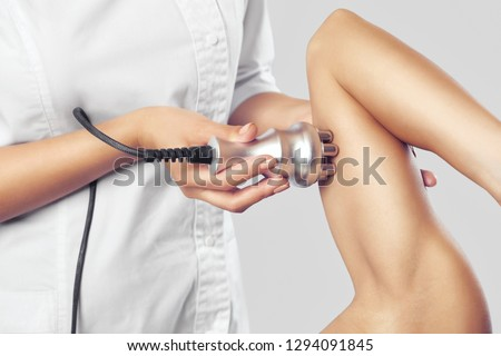 The doctor does the Rf lifting procedure on the upper arm of a woman in a beauty parlor. Treatment of overweight and flabby skin.