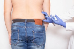 The doctor gives a subcutaneous injection to break down fat deposits on the sides of a man, lipolysis