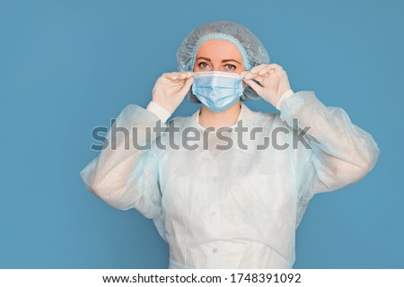 The doctor in a dressing gown, in medical gloves puts on a mask. Surgeon with clinical experience in healthcare, patient care. Copy space, isolated blue background. ストックフォト ©