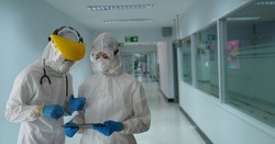 The doctor inquired about a communicable disease in the coronavirus vaccine covid-19.The doctor in the PPE protective suit asked the patient for personal information to test for covid