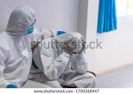 The doctor is comforting a colleague in the stress of work in PPE suit uniform has stress, Concept of Emotional stress of overworked doctor and medical care team during coronavirus
