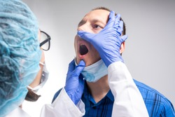 The doctor is examining the mouth, teeth, tongue of the patient. Doctor looking into mouth. Female doctor checking throat of male patient.