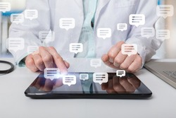 The doctor is in correspondence with messages on a tablet on a blurred background.