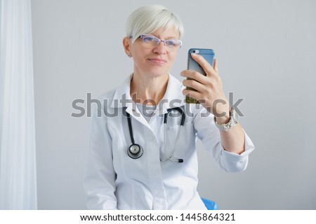 The doctor is on the video call mobile phone. Video Conferencing. Doctor's office and online patient reception