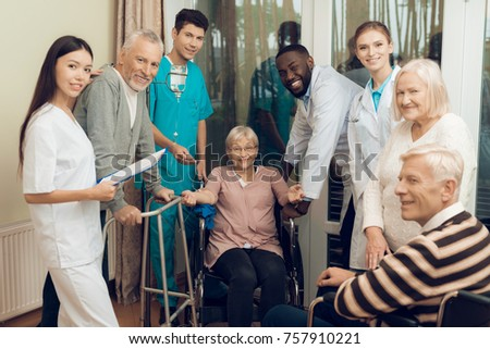 The doctor is talking to an elderly woman in a nursing home. He smiles. Nearby are medical staff and other senior men. They are looking at the camera. She is dripping a medical dropper.