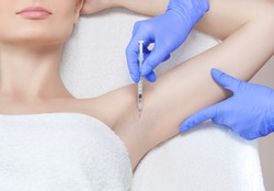 The doctor makes intramuscular injections of botulinum toxin in the underarm area against hyperhidrosis.