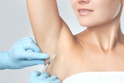 The doctor makes intramuscular injections of botulinum toxin in the underarm area against hyperhidrosis. Cosmetology skin care