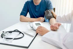The doctor measured blood pressure, the patient examined the heartbeat and talked about health care closely.