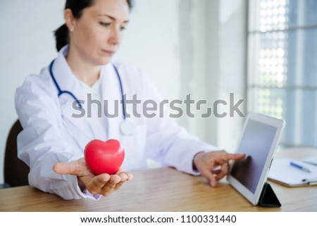 The doctor searching information in tablet with show sample heart. #1100331440