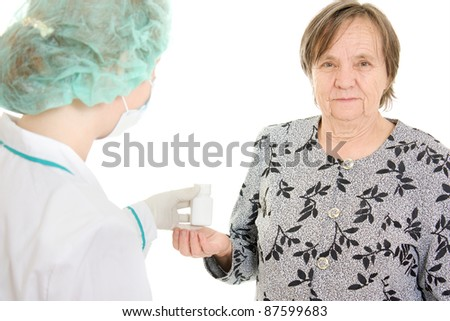The doctor takes a bottle of pills the old woman.