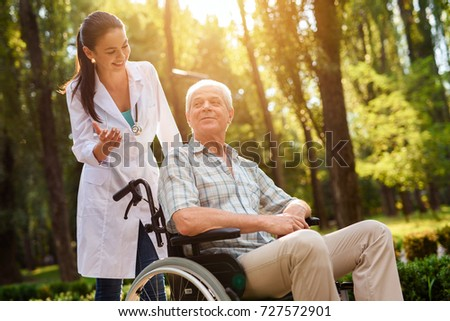 The doctor talks to the old man in wheelchair in the sunny park