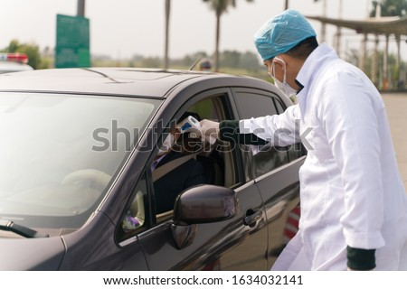 The doctors checking temperature at the temperature check post on the highway exit.