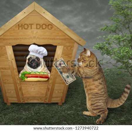 The dog in a chef hat sells hot dogs from a small wooden booth. The cat buys one.