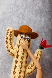 The doll's hand closes the mouth of a cowboy cactus with flowers. Feminism and emancipation concept.