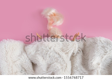 The dolls head and hands are visible from under the synthetic white fur. Minimalism concept, 80s style. Happy holidays greeting card