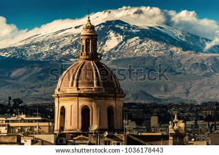 The dome of Cathedral in Catania on the background of volcano Etna in the snow.. The view of the city of Catania with the view of Etna volcano, Sicily, Italy. Catania the UNESCO World Heritage.