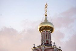 The dome of the church with a cross. Golden Dome and Golden Cross. Sunset with highlights on gold.