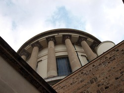 The dome of the Esztergom basilica is photographed from below next to a brick wall.