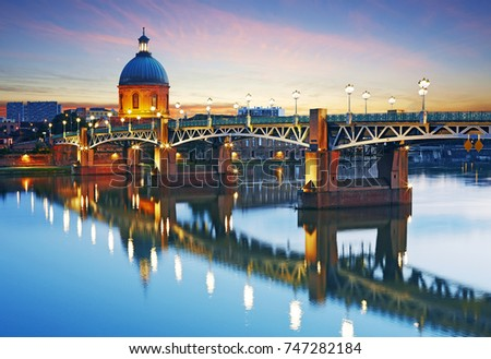 The dome of the 'Hopital de la Grave' illuminated at dusk over the Garonne River in Toulouse